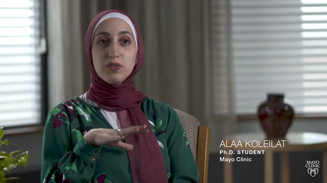Alaa Koleilat sits in a chair and talks, gesturing with her hands.