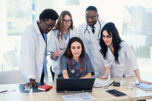 A team of young doctors group together to look at a laptop.