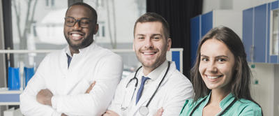 Three young researchers smile while standing with arms folded in a medical office.