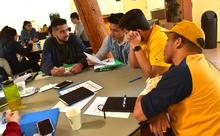 Group of students discussing an assignment at a round table.